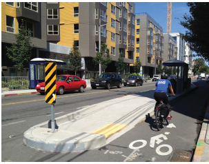 Bus loading zone on a raised median separates a dedicated bike lane from a side walk in Seattle.